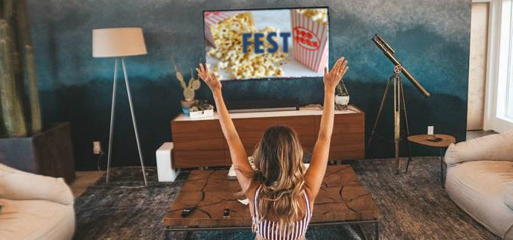 Image of lady in front of TV holding up arms